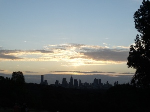The great outline of Melbourne city backlit by a cloud sunset, blue sky,